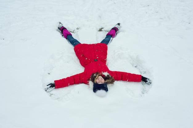 Horário de inverno, alegre garota se divertindo na neve, vista superior