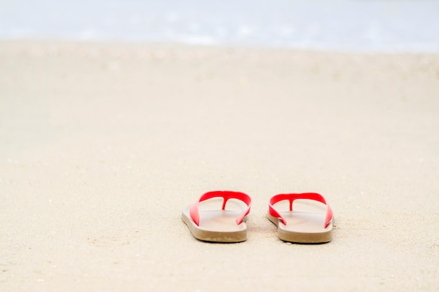 Horário de verão na praia com chinelos na praia de areia branca