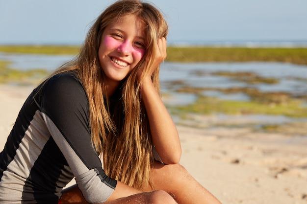 Horário de verão, resort e conceito de emoções positivas. linda mulher de cabelos compridos com expressão alegre, tem máscara surf zic