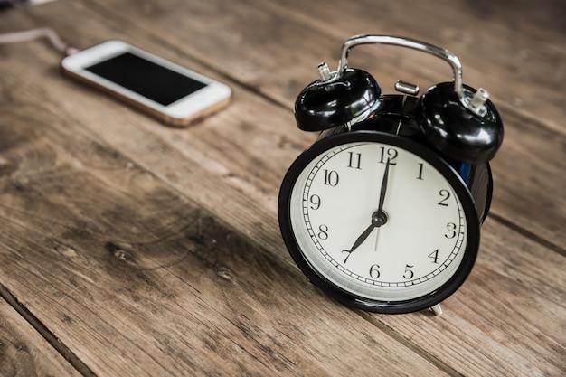 Horas do pulso de disparo às 7 horas da manhã na tabela de madeira com o telefone esperto que carrega no fundo do borrão do café.