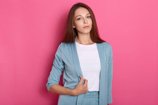 Horizontal confiante bonita empresária confiante, colocando a mão no casaco