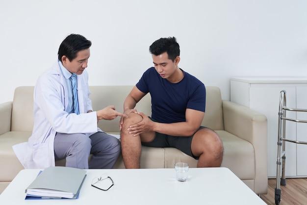 Horizontal médio plano longo de jovem asiático sentado no sofá no consultório médico, tendo uma consulta sobre dor no joelho