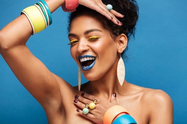 Horizontal mulata adorável com maquiagem colorida e cabelos cacheados em coque sorrindo e demonstrando acessórios nos braços, isolados sobre azul