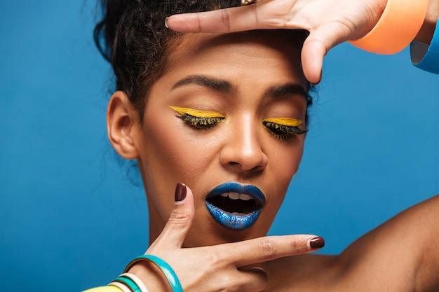 Horizontal mulata elegante com maquiagem colorida e cabelos cacheados em coque de mãos dadas perto do rosto isolado, sobre parede azul