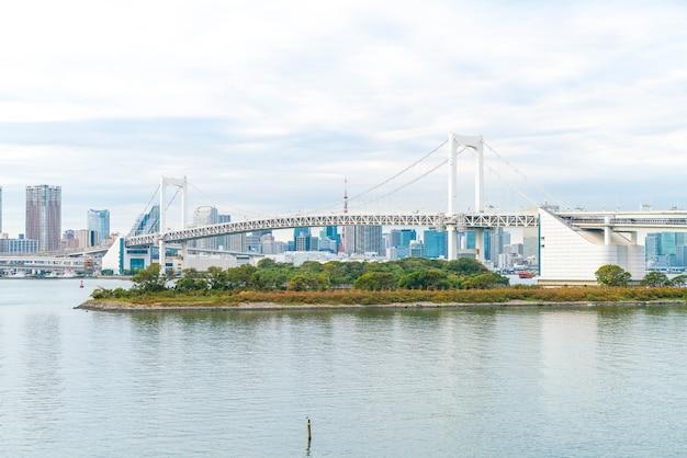 Horizonte de tóquio com a torre de tóquio e a ponte do arco-íris.