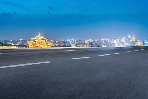 Horizonte do pavimento da via expressa e cenário noturno da paisagem arquitetônica urbana