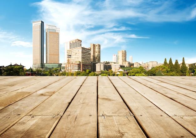 Horizonte panorâmico e edifícios com tabuleiro de madeira vazio