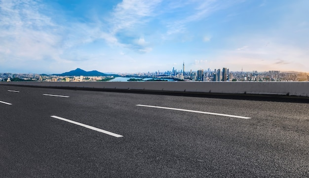 Horizonte panorâmico e estrada de asfalto vazia com edifícios modernos