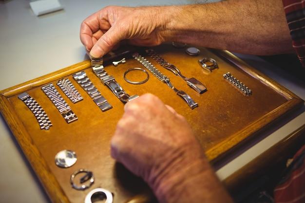 Horólogo organizando pulseira de relógio na placa de madeira