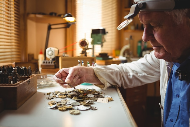 Horólogo selecionando um mostrador de relógio com uma pinça