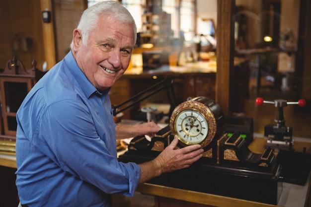Horólogo, verificando um relógio na oficina