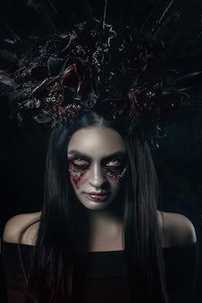 Horror terrível retrato de mulher de vampiro de halloween. senhora de bruxa de vampiro de beleza com sangue na boca posando na floresta profunda. projeto de arte da moda. segura uma vela nas mãos e lê maldições