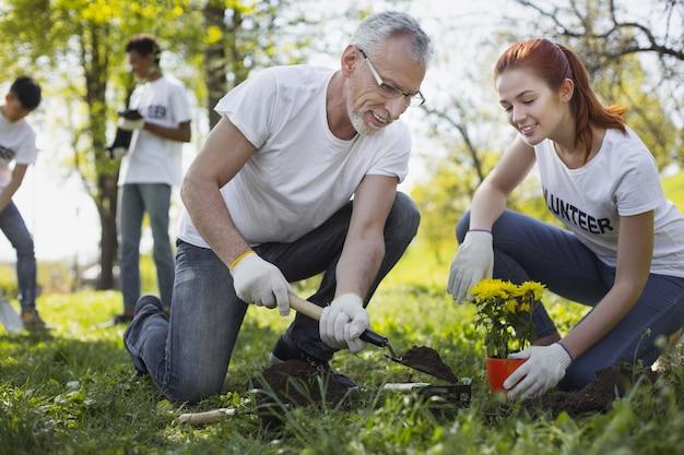 Horta comunitária. dois voluntários alegres plantando flores e sorrindo