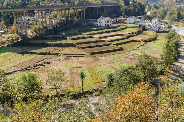 Hortas perto de casas de aldeia perto do rio e rodovia