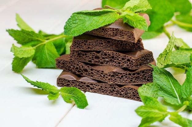 Hortelã fresca e chocolate poroso em uma superfície branca