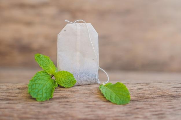 Hortelã fresca e saquinho de chá na mesa de madeira