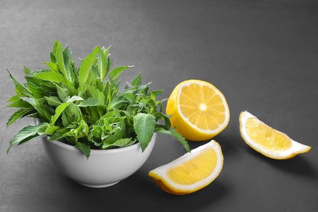 Hortelã fresca em uma tigela branca com limão em um fundo preto
