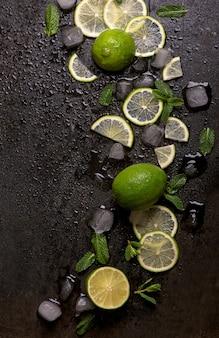 Hortelã fresca, limão e gelo em um fundo preto.