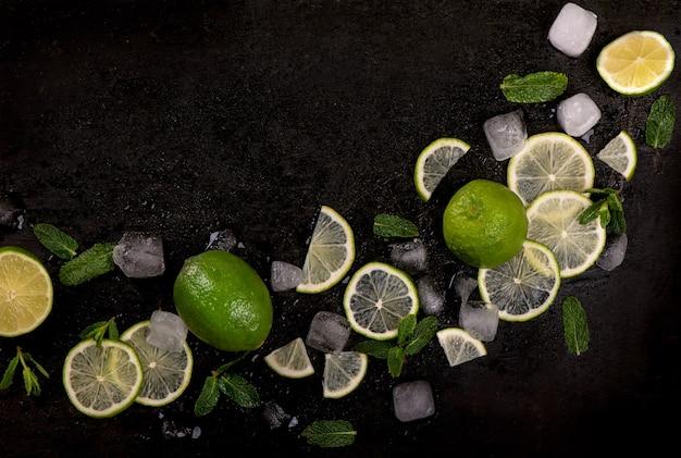 Hortelã fresca, limão e gelo em um fundo preto. Foto Premium