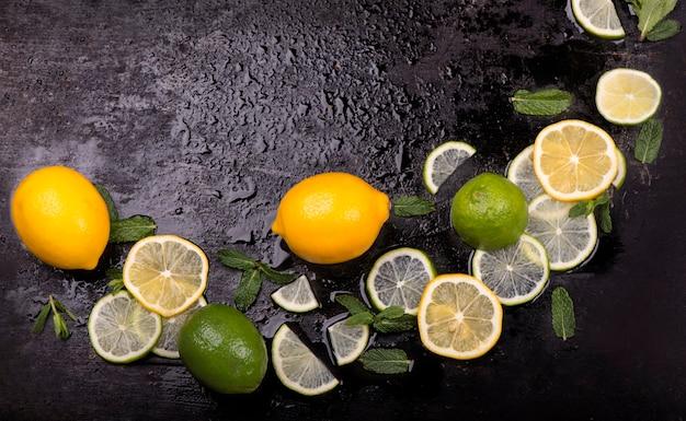 Hortelã fresca, limão e gelo em uma mesa preta. vista do topo