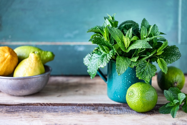 Hortelã fresca orgânica e erva-cidreira em uma caneca de metal e limas e limões em uma mesa de madeira. copie o espaço