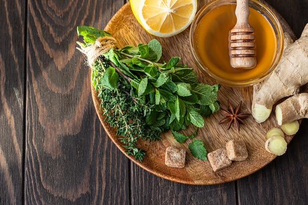 Hortelã, tomilho, raiz de gengibre, limão, mel e açúcar mascavo. ingredientes para fazer chá de gengibre ou ervas.