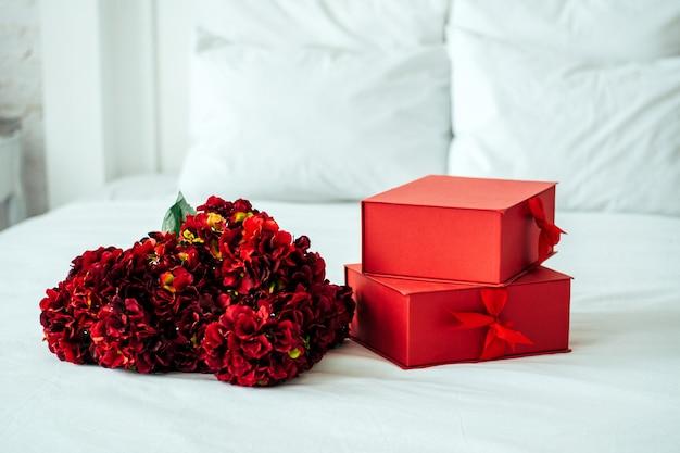Hortênsia é vermelha em uma cama branca e caixas