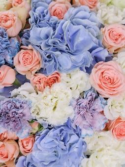 Hortênsias azuis, rosas bege, eustoma branco e cravos incomuns são combinados em um buquê