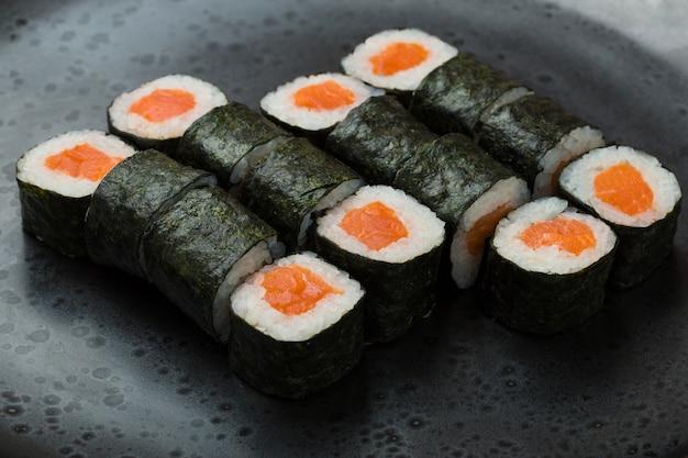 Hosomaki rola o close up em uma placa preta com foco seletivo. rolos com algas, arroz, salmão