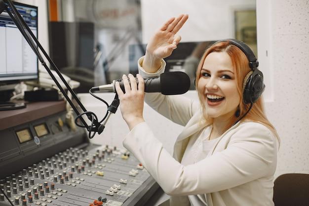 Hospedeira se comunicando no microfone. mulher no estúdio de rádio.