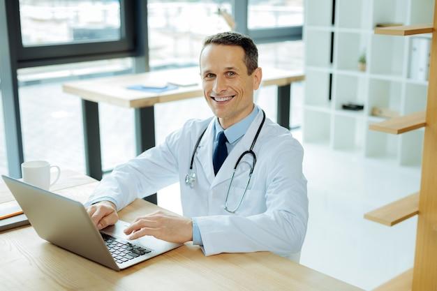 Hospital moderno. belo e simpático médico inteligente sentado à mesa e sorrindo enquanto usa seu laptop
