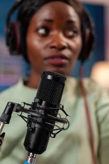 Host africano de programa online usando microfone falando com entretenimento de ouvintes. falando durante a transmissão ao vivo, blogueiro discutindo no podcast usando fones de ouvido.
