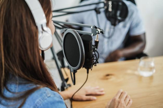 Hosts multirraciais dando entrevistas enquanto transmitem podcast juntos no estúdio doméstico - foco no microfone