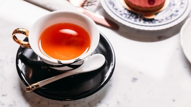 Hot apple tea servido em copo de vintagr de porcelana com bolo de mousses na mesa de tampo de mármore.
