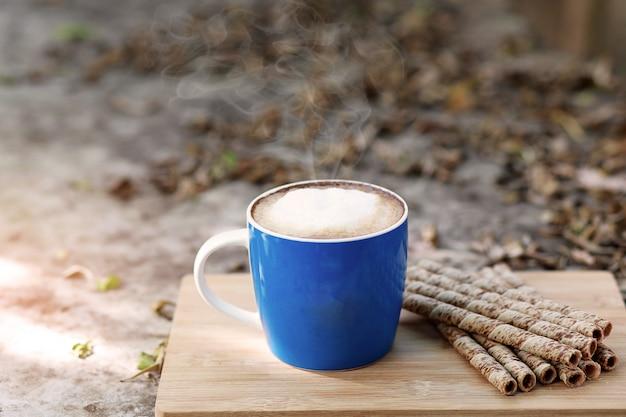 Hot latte fresh coffee em uma caneca azul com espuma de leite, fumaça e crocante chocolate roll sobremesas