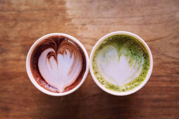 Hot latte matcha e latte art café tão delicioso em cima de fundo mesa de madeira
