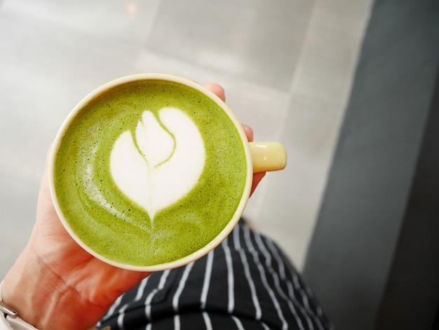 Hot matcha chá verde com leite em uma mão de mulher