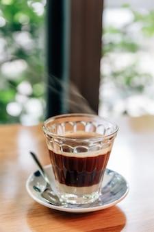 Hot serve café vietnamita: mistura de café preto com leite condensado em vidro transparente.