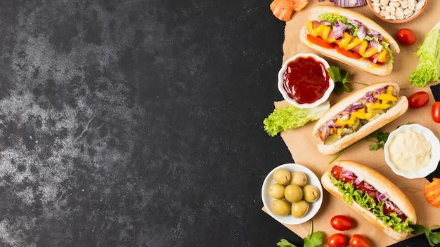 Hotdog apetitosos na mesa de ardósia preta