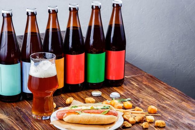 Hotdog e cerveja em uma placa de madeira.