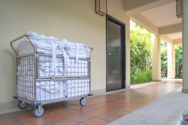 Hotel de empregada com carrinho de estacionamento em frente ao quarto com toalha limpa e roupão pronto para trocar e arrumar o quarto.