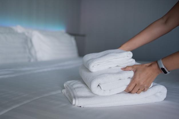 Hotel de limpeza, toalha de banho na cama branca, serviço de quarto
