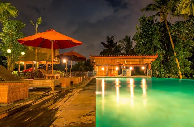 Hotel na selva tropical. piscina noturna. palmeiras, guarda-sóis, espreguiçadeiras e bar. ninguém