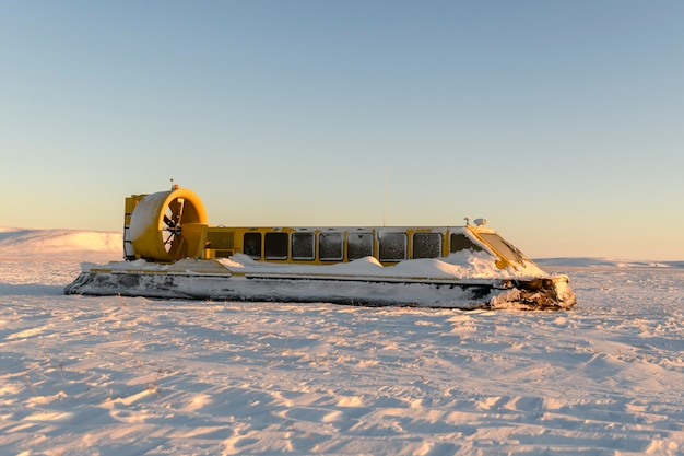 Hovercraft na tundra de inverno. almofada de ar na praia. navio flutuante amarelo sob a neve.