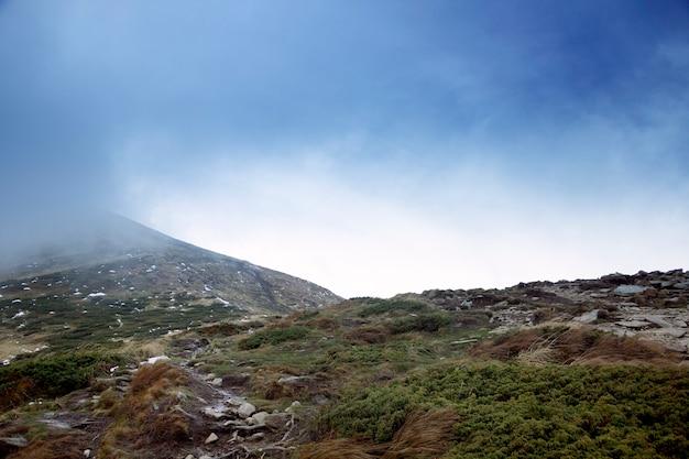 Hoverla, topo de uma montanha parcialmente coberta de neve e nevoeiro matinal.