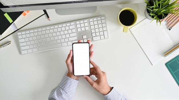 Hs do homem segurando a tela vazia de smartphone na mesa de escritório com vista superior.