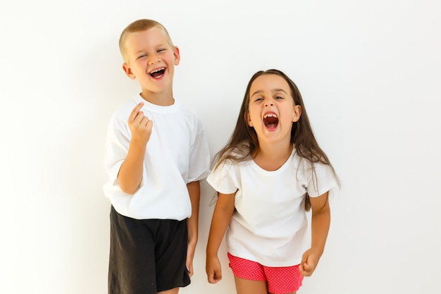 Huggg bonito pequeno da menina do menino que joga no fim branco, feliz da família isolado acima. irmão e irmã sorrindo