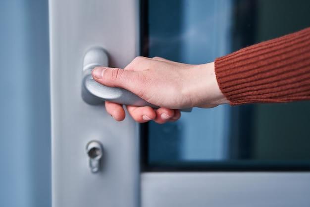 Humano abre a porta. mão na maçaneta da porta