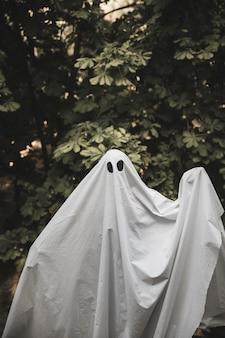 Humano em traje de fantasma com as mãos levantadas
