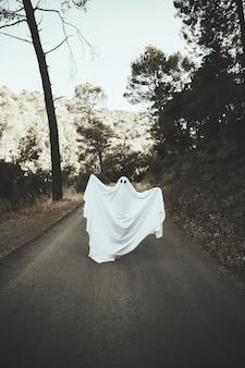 Humano em traje fantasma levantando as mãos na rota rural
